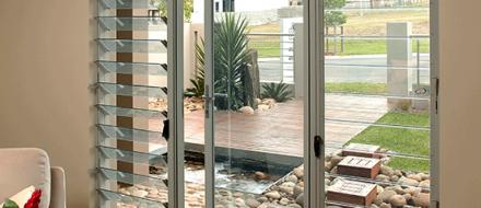 Hinged door between louver windows