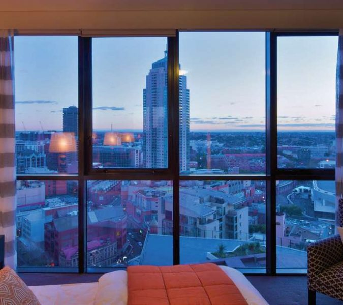 room with large awning windows and view of the city
