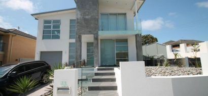 front view of a house with bluish glass and aluminum windows and doors